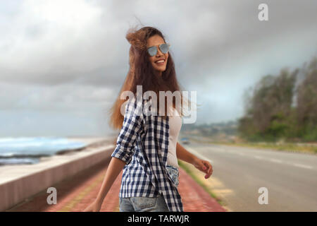 Woman wearing sunglasses looking back while walking on a road - Stock Image