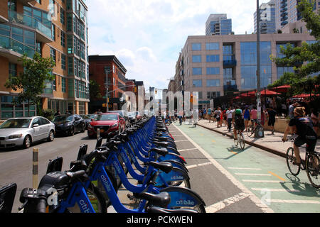 People dock CitiBike bicycles as cyclists pass on an adjacent bike lane next to Smorgasburg in Williamsburg, Brooklyn on JULY 8th, 2017 in New York, U - Stock Image