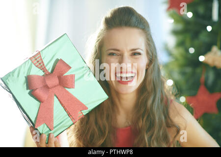 Portrait of smiling trendy woman in red dress with green Christmas present box near Christmas tree - Stock Image