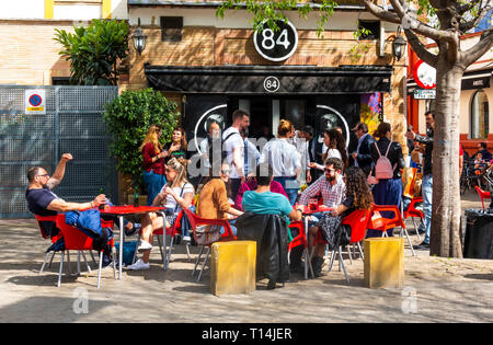 Friends gathered at outdoors tables at a tapas bar in Seville - Stock Image