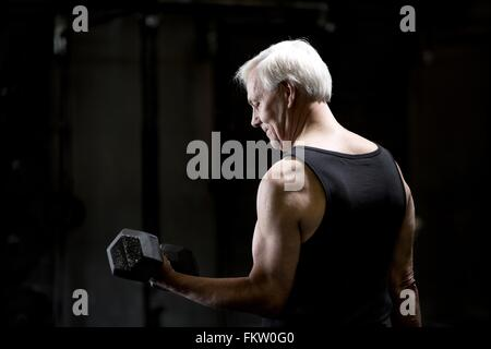 Senior man doing bicep curls with dumbbell in dark gym - Stock Image