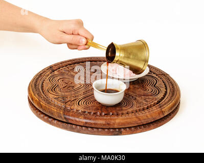 She is serving a black coffee from Turkish coffee pot (a jazve or an ibrik), and pouring it in Turkish coffee cup (a fildzan). - Stock Image