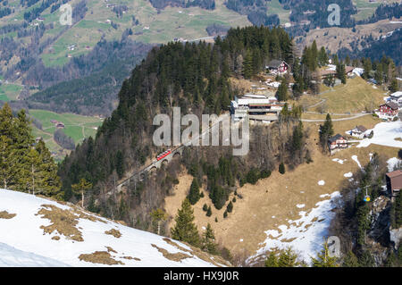 Red funicular and yellow cable car arriving at their respective top stations in Stoos, a mountain village in central - Stock Image
