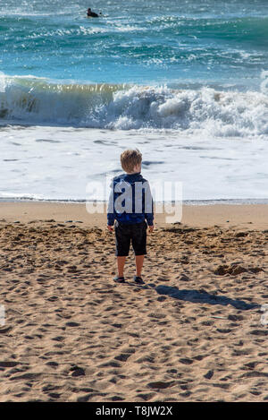 A young boy standing alone on the shoreline gazing out to sea on Fistral Beach in Newquay in Cornwall. - Stock Image