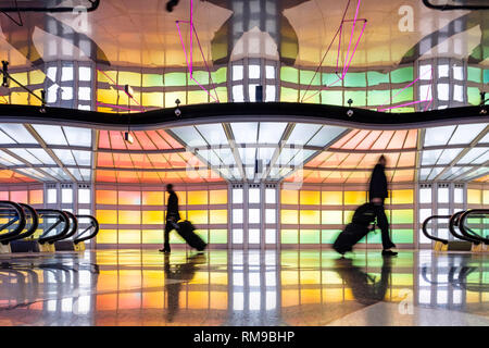 Air passengers, business people walking, colourful neon lights art installation by Michael Hayden, pedestrian tunnel, Chicago O'Hare Airport Terminal. - Stock Image