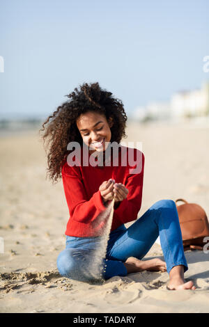 Happy young woman sitting on the beach - Stock Image