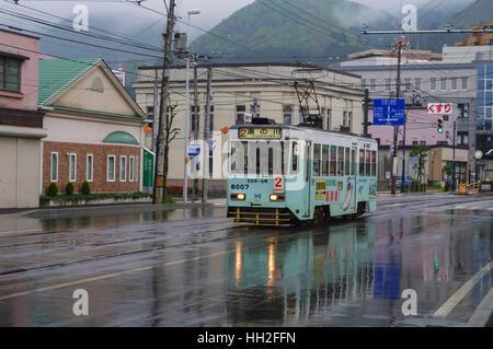 Streetcar of the Hakodate Tram running on Kaikyo Dori street on a rainy day. Hakodate, Hokkaido, Japan. - Stock Image