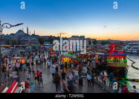 Istanbul, Turkey - August 14, 2018: People eat and walk at the Eminonu Square at dusk on August 14, 2018 in Istanbul, Turkey - Stock Image