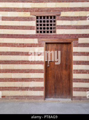 Background of old wall with red bricks and yellow stones, wooden closed door and window, Cairo, Egypt - Stock Image