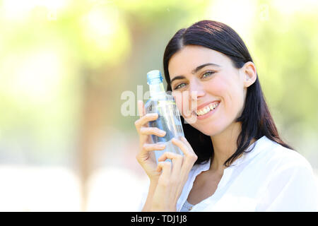 Happy woman holding a bottle of water looking at you standing in a park with a green background - Stock Image