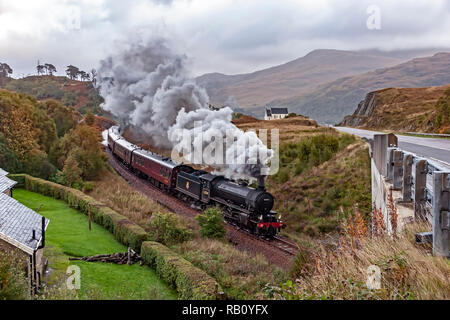 K1 steam engine No. 62034 pulls the Jacobite steam train past the famous church at Polnish at A830 en route to Mallaig from Fort William in Scotland - Stock Image