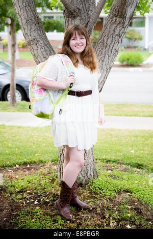 Portrait of teenage girl (13-15) with backpack - Stock Image