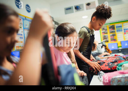 Junior high school girl students with backpacks in classroom - Stock Image