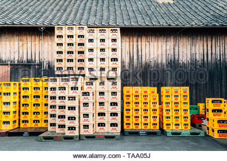 Shikoku, Japan - April 17, 2019 : Yellow crates full of beer bottles and Japanese traditional house - Stock Image