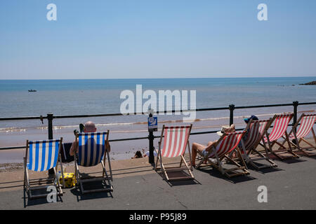 Holidaymakers enjoy a hot summer afternoon at The Esplanade in Sidmouth, East Devon, UK - Stock Image