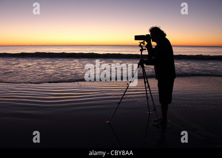 SILHOUETTE OF A MAN TAKING A PHOTO AT SUNRISE ON A BEACH HORIZONTAL BDA - Stock Image