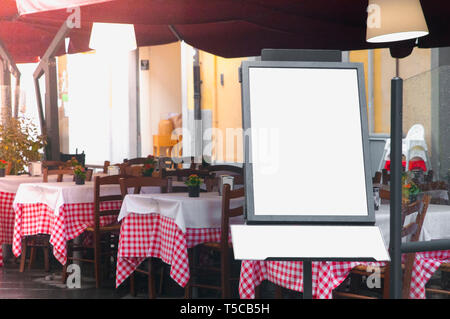 Italian street restaurant with blank menu board on a stand - Stock Image