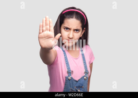 Stop. Portrait of angry beautiful brunette young girl in casual, pink t-shirt and blue denim overalls standing, looking and blocking with hand. indoor - Stock Image