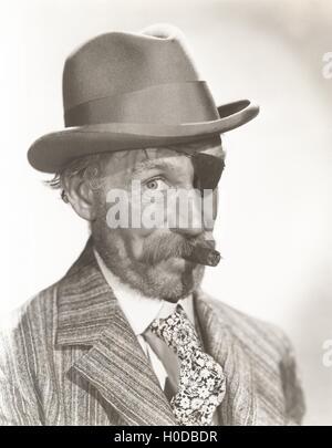Man wearing eye patch and fedora smoking cigar - Stock Image
