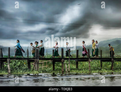 A group of school childen walk along a jetty at Inle Lake, Myanmar. - Stock Image