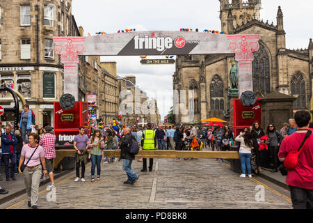 Edinburgh, Scotland, UK. 7th August 2018. Entrance to the Virgin Money Fringe on the Mile street performance space on Edinburgh's Royal Mile during the 2018 Edinburgh Fringe Festival. Street acts and artists, performing alongside promoters of Fringe Festival events, ply the streets of Edinburgh Festival, providing entertainment and amusement to the many visitors to the Fringe. Credit Joseph Clemson, JY News Images/Alamy Live News - Stock Image