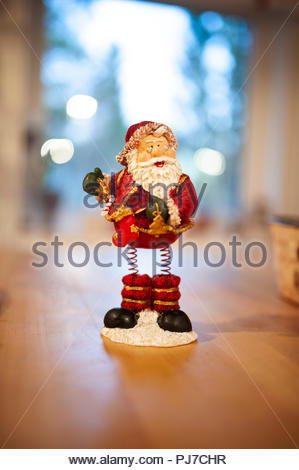 A vintage toy, of father Christmas with iron springs instead of legs. Bokeh in the background. - Stock Image