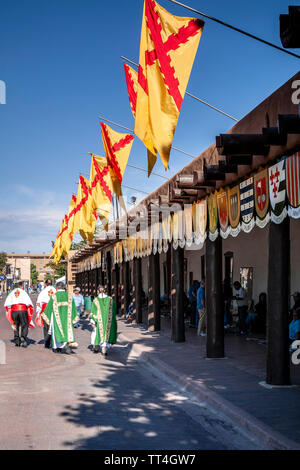 Priests walking in front of Palace of the Governors festooned with flags and coats of arms, Fiesta de Santa Fe, Santa Fe, New Mexico USA - Stock Image