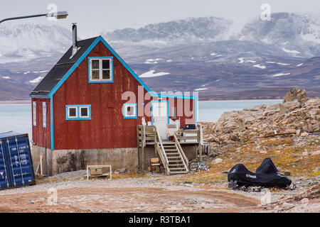 Greenland. Scoresby Sund. Ittoqqortoormiit. Colorful house with snowmobile outside. - Stock Image