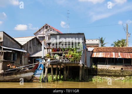 Typical Vietnamese tin shack stilt houses on riverside of Co Chien River in Mekong Delta. Cai Be, Tien Giang Province, Vietnam, Asia - Stock Image