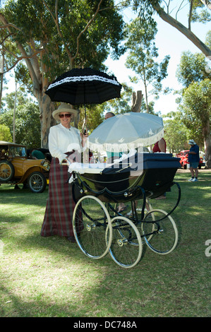 Woman in period dress with a vintage Osnath coachbuilt pram. - Stock Image