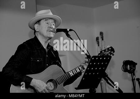 Hank Wangford in black and white live at the Stoke Newington Music Festival in St Paul's Church with a straw hat and acoustic guitar - Stock Image
