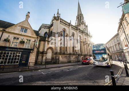 A First bus heads out of historic Broad Street in Bath with a red van in an empty car-free street with St Michael Without Church and the Saracens Head - Stock Image