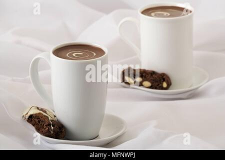 White porcelain cups with drinking chocolate. Almond and chocolate biscoti in saucer. Studio shot.      Ref: CRB538_103609_0008  COMPULSORY CREDIT: Ma - Stock Image