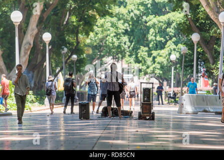 Jan 2019: People walking through the middle path of central Sydney's Hyde Park while a busker plays music and a person takes his photograph - Stock Image