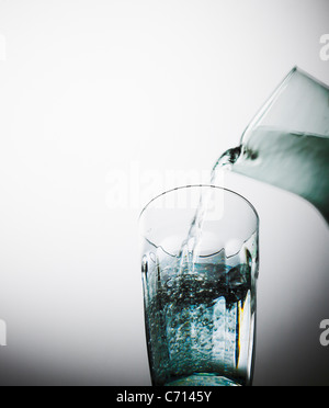 water being poured from a jug into a glass. - Stock Image