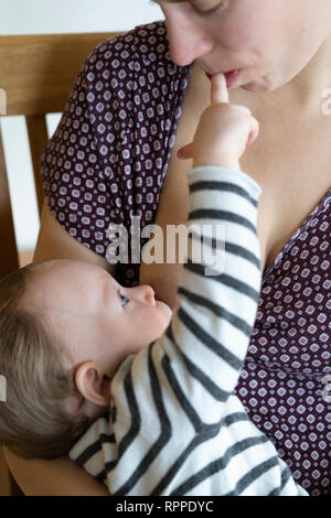 An eleven month old baby girl breastfeeding and playing / interacting with her mother - Stock Image