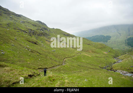 A lone female walking in the upper reaches of Glen Finnan on a cold and damp november day in the hills - Stock Image
