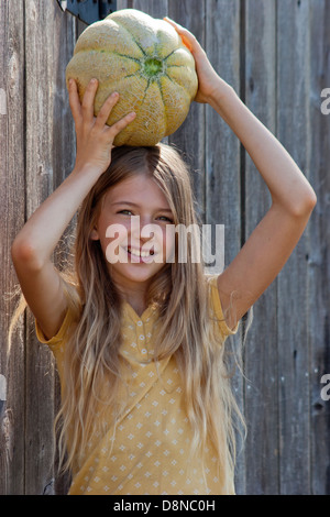 Girl posing with a heirloom cantaloupe on her head in front of the gray wood fence - Stock Image