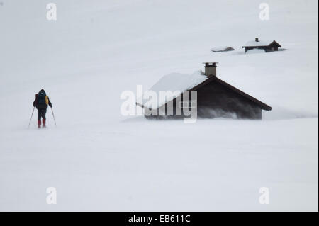 man in snow shoes with heavy pack approaching mountain huts in winter mountain landscape with wind blown snow in - Stock Image