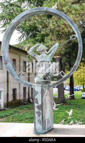 Contemporary war memorial statue containing a wire or rope-bound prisoner contained within a circle. A white dove perches atop the circle. Public art  - Stock Image