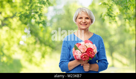 happy smiling senior woman with flowers - Stock Image