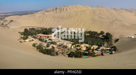 Huacachina oasis landscape panorama. Windy and sand over the air. Ica desert, Peru. - Stock Image