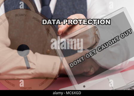 Business man sittig behind desk pushing virtual screen with the words data protection and DONT GET CAUGHT OUT . - Stock Image