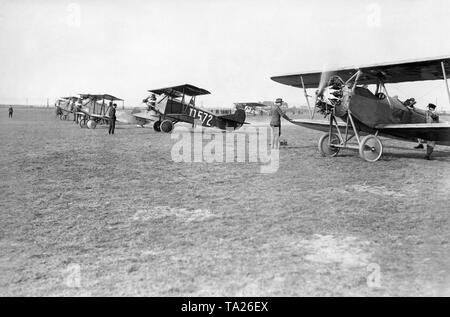 Four biplanes before the start on the airfield Berlin-Staaken. The third flight from the front carries the lettering'UFA Wochenschau'. In the background, a Dornier Komet of Lufthansa. - Stock Image