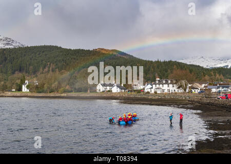 Lochgoilhead, Argyll and Bute, Scotland - young people braving the chilly waters of Loch Goil underneath a rainbow during raft building activity - Stock Image