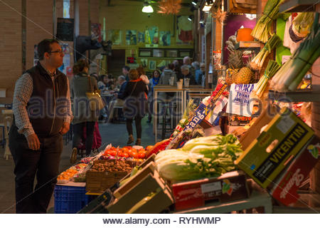 Stallholder at his vegetable stall in Triana Market with people at cafe behind - Stock Image