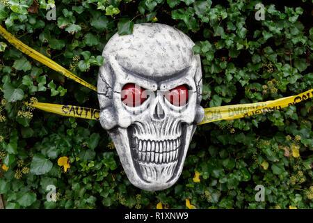 Frightening Halloween grinning skull decoration in a garden - Stock Image