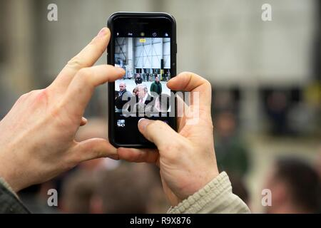 A U.S. service member takes a cell phone photo of U.S. President Donald Trump during stop-over at Ramstein Air Force Base following a surprise visit to Iraq December 26, 2018 in Ramstein-Miesenbach, Germany. The president and the first lady spent about three hours on Boxing Day at Al Asad, located in western Iraq, their first trip to visit troops overseas since taking office. - Stock Image