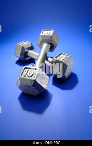 A pair of exercise metal free weights on a blue exercise mat. - Stock Image