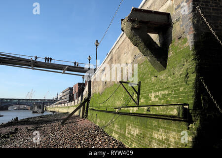 View of people standing on Millennium Bridge & algae covered river wall on north bank of River Thames at low tide in London England UK  KATHY DEWITT - Stock Image